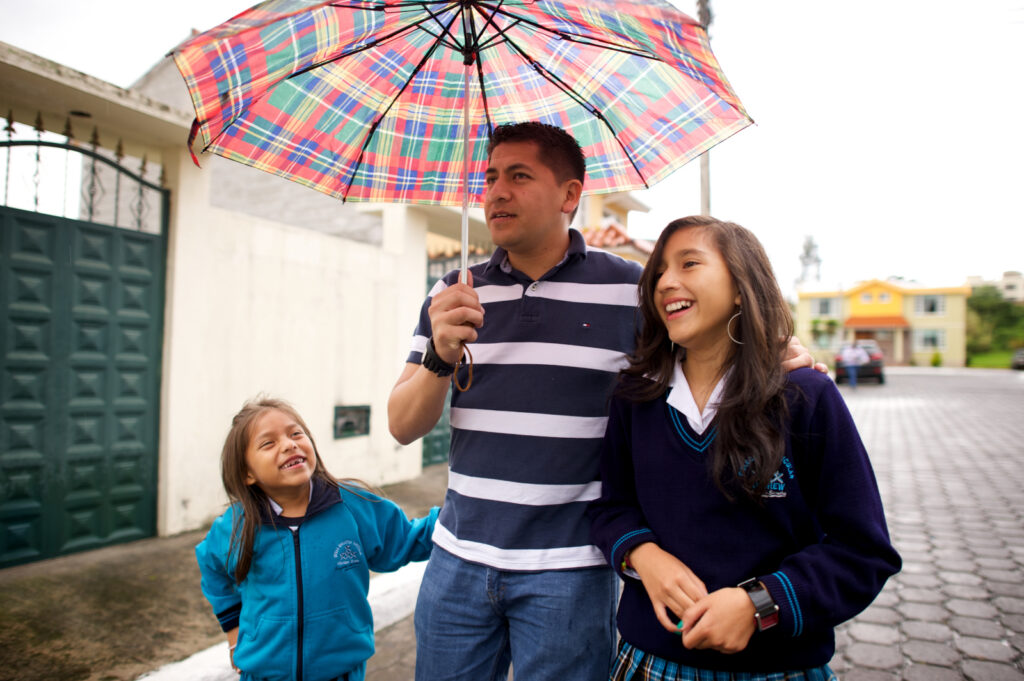 A father and two daughters walk down the road under an umbrella.