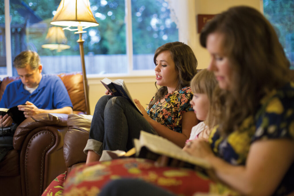 A young woman reads from the Book of Mormon while family members follow along.