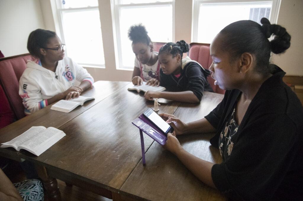Los miembros de la familia se sientan juntos para leer las Escrituras de libros y teléfonos inteligentes.
