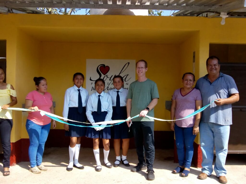 Kenneth Grover, center right, stands with a group of students to cut a ribbon after completing a toilet building project for one of the schools where the SOYLA Foundation sponsors scholarships in Guatemala.