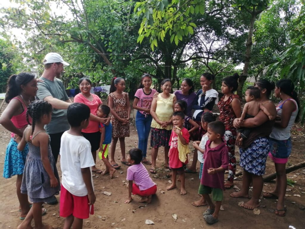 Kenneth Grover, left, meets with community members in one of the areas where he sponsors scholarships for primary school-aged children in Guatemala.