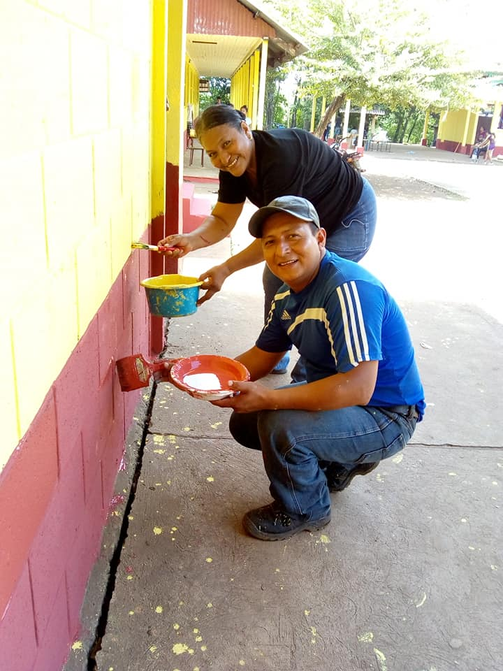 Community members help paint at their local school in Guatemala as part of a project to upgrade the schools sponsored by the SOYLA Foundation.