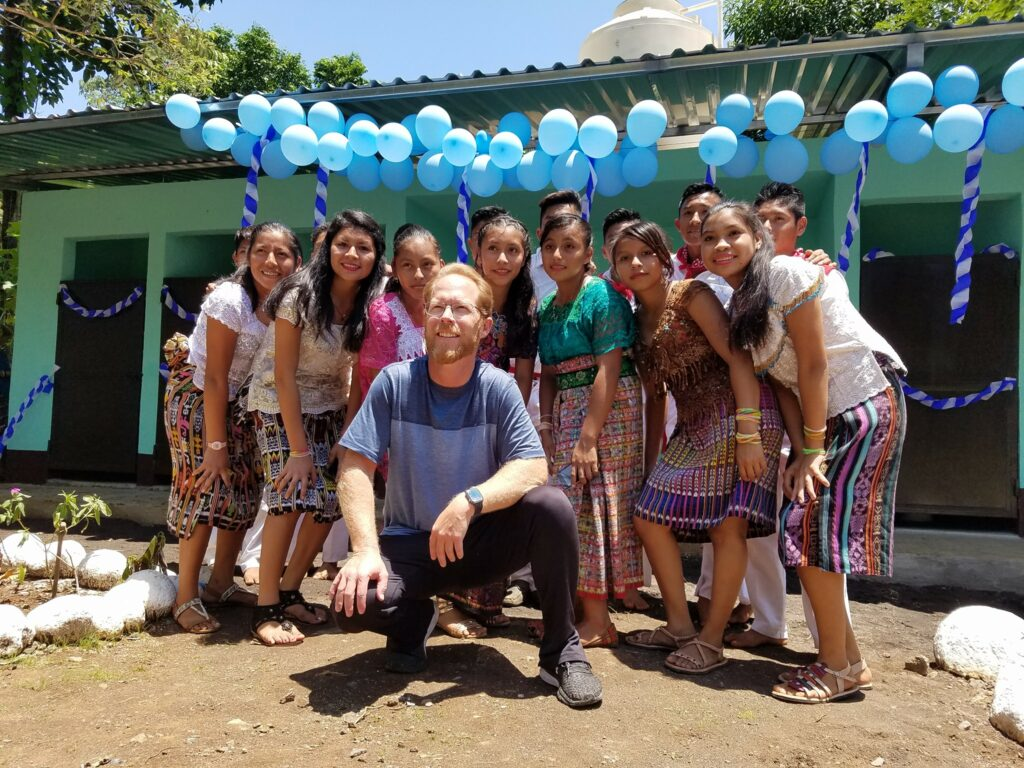 Kenneth Grover, center, poses for a photo with students at their school in Guatemala where the SOYLA Foundation helped to build new facilities and sponsors scholarships for students.