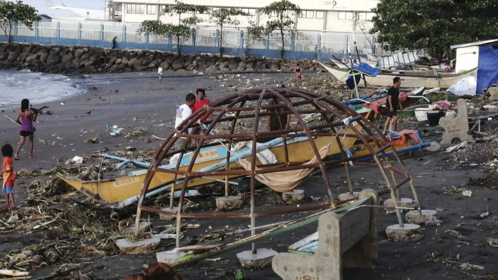 Residents walks beside an outrigger and playground equipment that were damaged by Typhoon Phanfone along a coastline in Ormoc city, central Philippines, on Thursday, Dec. 26, 2019. The typhoon left over a dozen dead and many homeless.