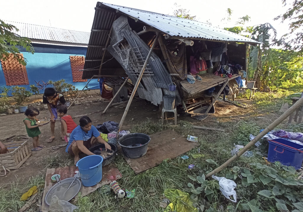 Residents stay outside their home that was damaged by Typhoon Phanfone at Concepcion town, Iloilo province, central Philippines, on Friday, Dec. 27, 2019. A strong typhoon that barreled through the central Philippines left dozens dead and missing, and forced thousands to flee their homes, devastating Christmas celebrations in the predominantly Roman Catholic country.