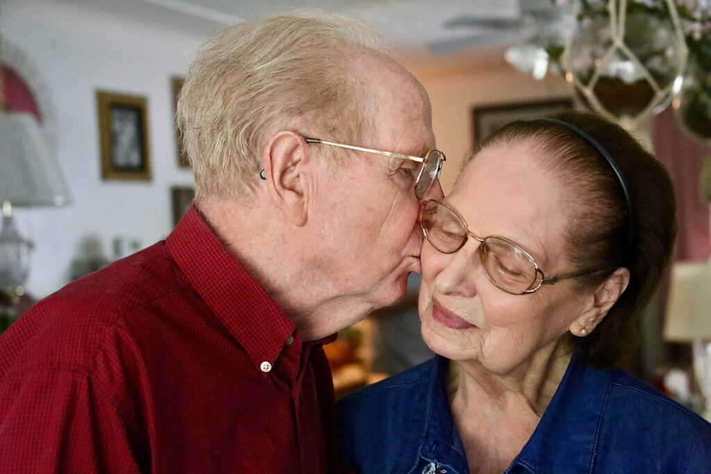 Elden Wood kisses the cheek of his wife, Picola Wood, at their home. Together they have served six Latter-day Saint missions.