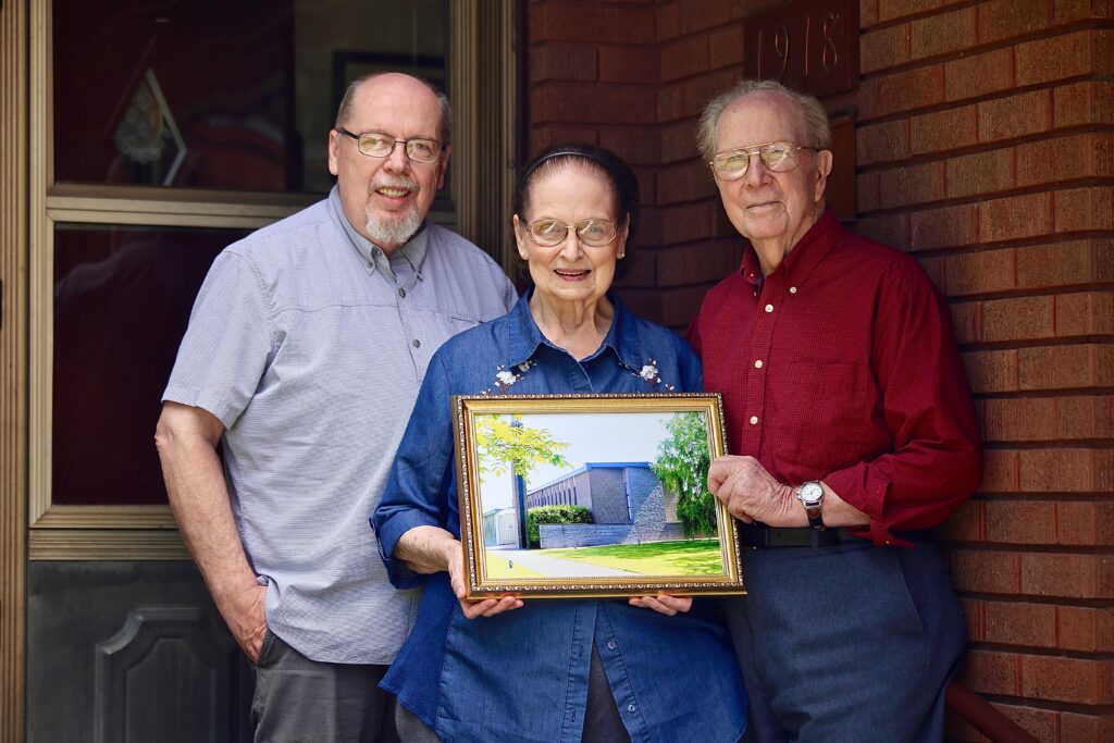 Elden and Picola Wood stand with their son, Alan, who accompanied his parents to Belgium where Elden supervised the building of the chapel shown in the photo.