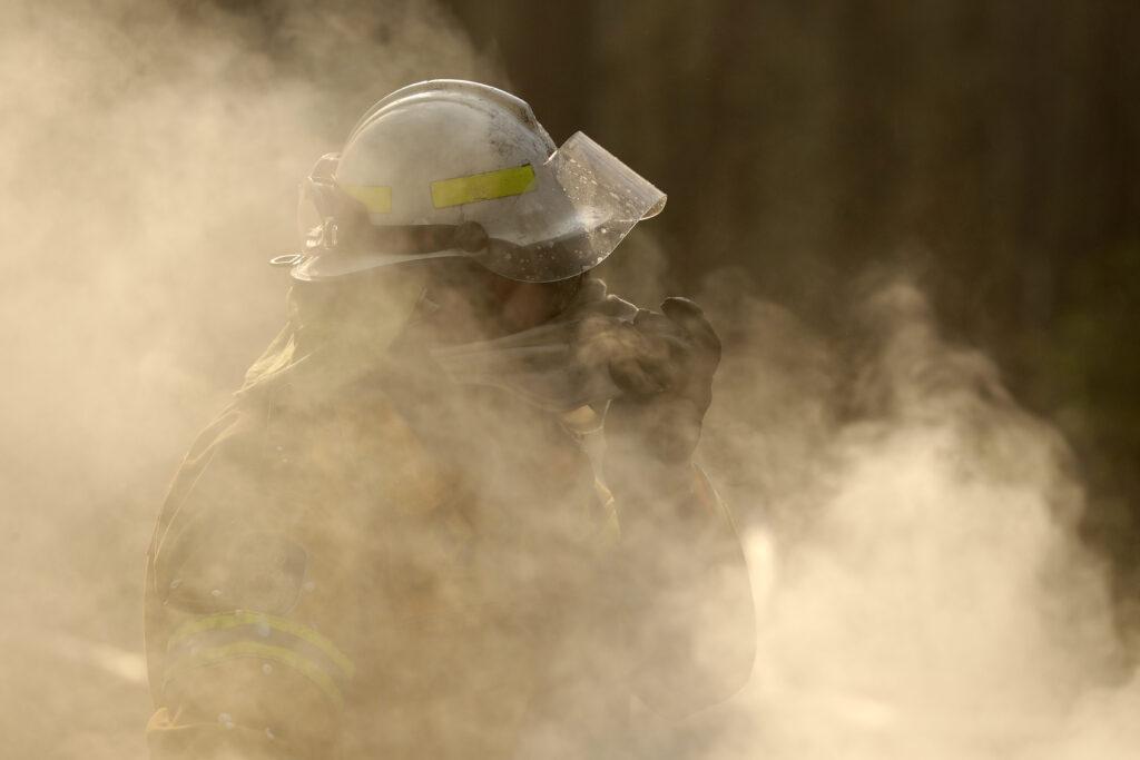 A firefighter covers his face from block smoke as he battles a fire near Bendalong, Australia, Friday, Jan. 3, 2020.