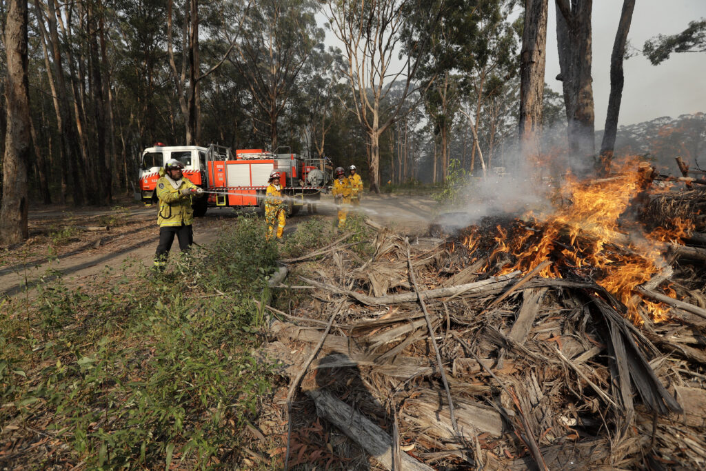 Firefighters battles a fire near Bendalong, Australia, Friday, Jan. 3, 2020. Navy ships plucked hundreds of people from beaches and tens of thousands were urged to flee before hot, windy weather worsens Australia's devastating wildfires.