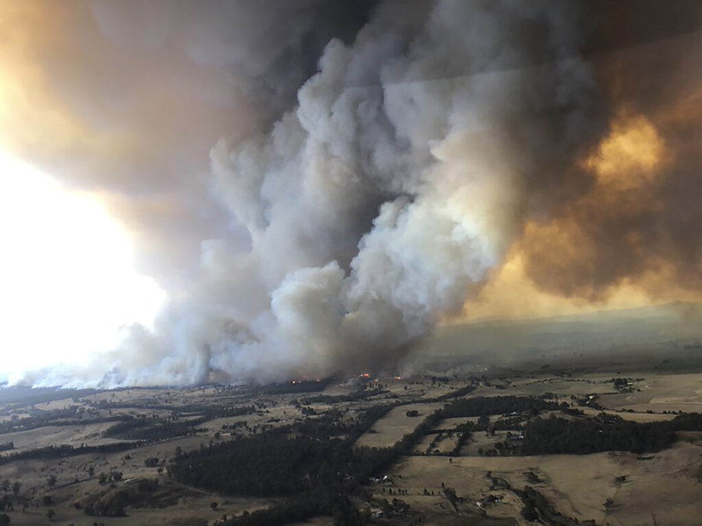 In this Monday, Dec. 30, 2019, aerial photo, wildfires rage under plumes of smoke in Bairnsdale, Australia. Thousands of tourists fled Australia's wildfire-ravaged eastern coast Thursday ahead of worsening conditions as the military started to evacuate people trapped on the shore further south.