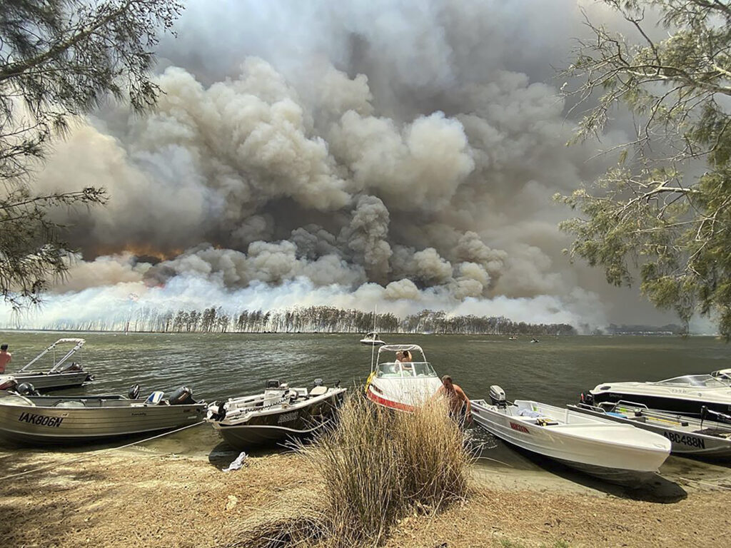 Boats are pulled ashore as smoke and wildfires rage behind Lake Conjola, Australia, Thursday, Jan. 2, 2020. Thousands of tourists fled Australia's wildfire-ravaged eastern coast Thursday ahead of worsening conditions as the military started to evacuate people trapped on the shore further south.