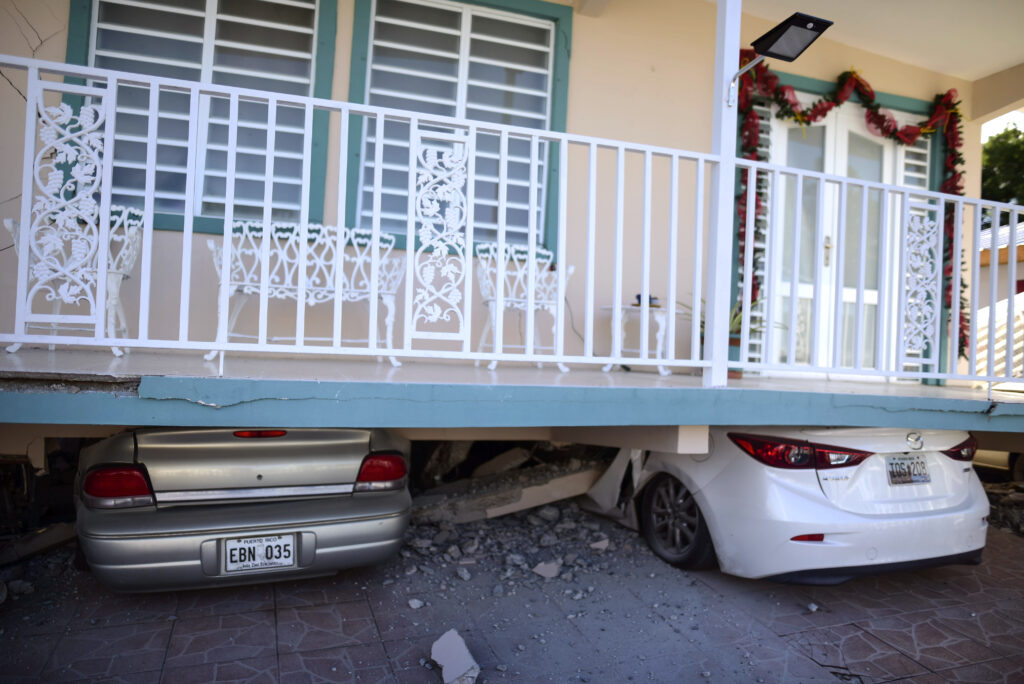 Cars are crushed under a home that collapsed after an earthquake hit Guanica, Puerto Rico, Monday, Jan. 6, 2020. A 5.8-magnitude quake hit Puerto Rico before dawn Monday, unleashing small landslides, causing power outages and severely cracking some homes. There were no immediate reports of casualties.