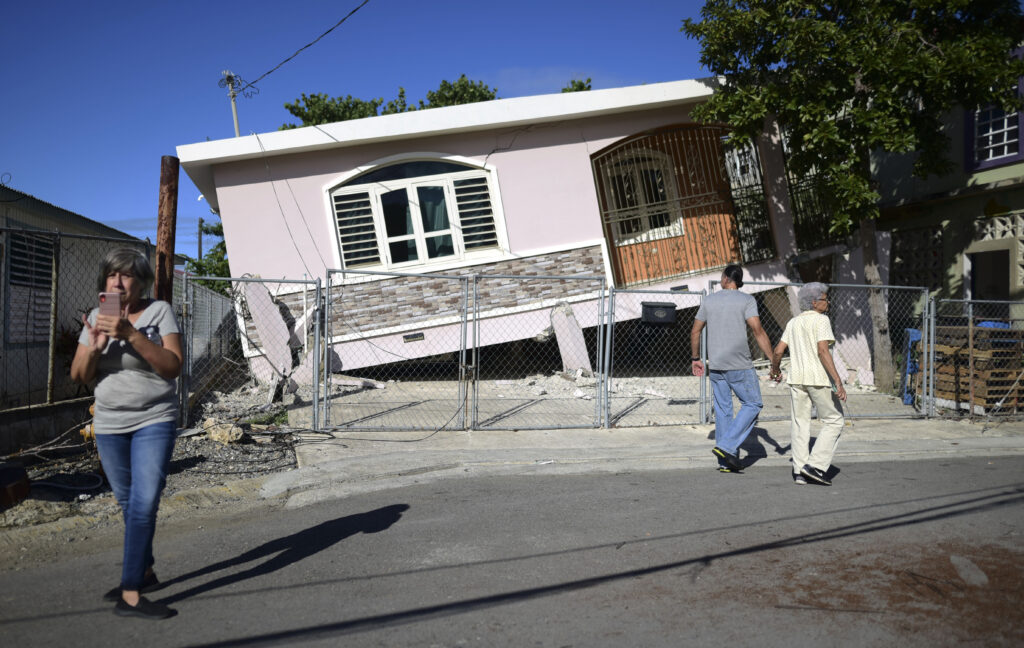 Residents survey damage where a home partially collapsed after an earthquake hit Guanica, Puerto Rico, Monday, Jan. 6, 2020. A 5.8-magnitude quake hit Puerto Rico before dawn Monday, unleashing small landslides, causing power outages and severely cracking some homes. There were no immediate reports of casualties.