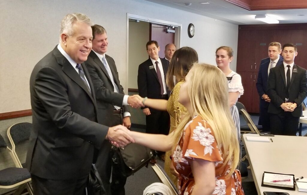 Elder Brent H. Nielson, left, and Elder James R. Rasband greet members of the Tennessee Nashville mission leadership council in a morning meeting as part of a mission tour on Sept. 19, 2019, in Brentwood, Tennessee.