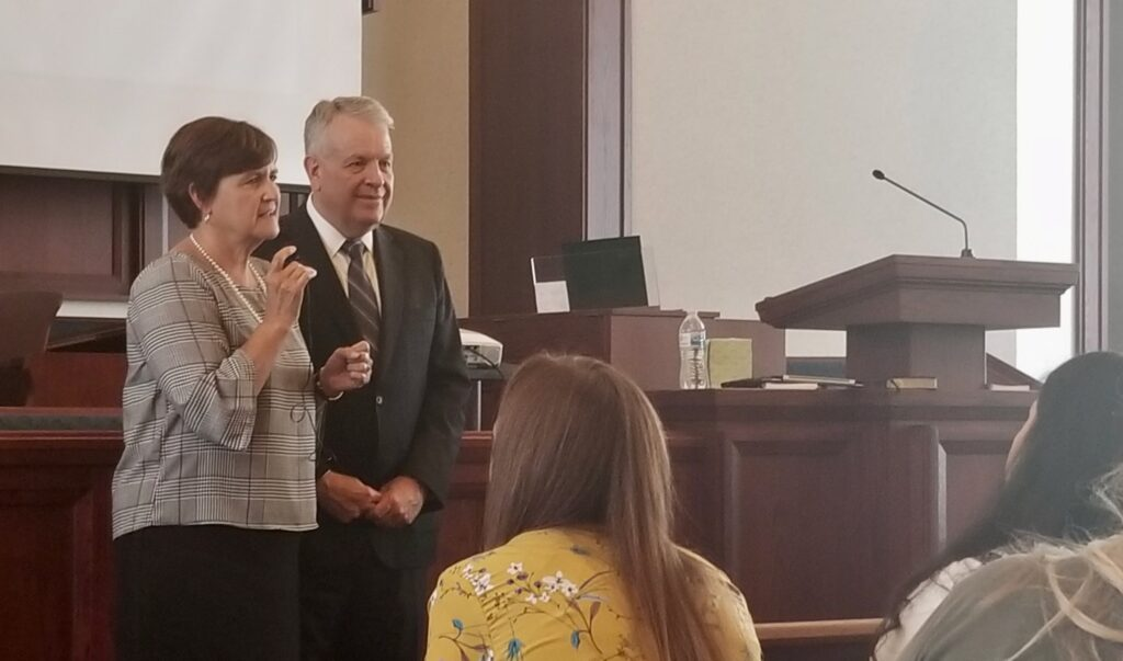 Sister Marcia Nielson, left, bears her testimony to Tennessee Nashville Mission missionaries as her husband, Elder Brent H. Nielson listens, during a mission tour meeting in Brentwood, Tennessee, on Sept. 19, 2019.
