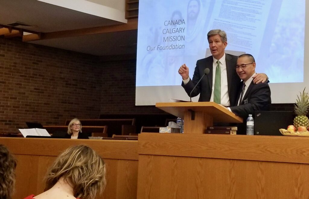 Elder S. Gifford Nielsen makes it a point to join Canada Calgary Mission President Stephen A. Keung at the pulpit during a mission tour meeting on Oct. 31, 2019, in Calgary, Canada.