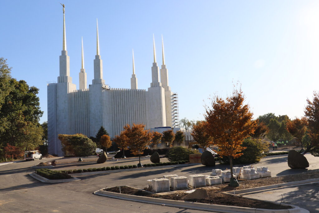October, 2019, photo of the Washington D.C. temple during the renovation period. Scaffolding is found on the building's exterior and new trees are ready to be planted in the parking area.