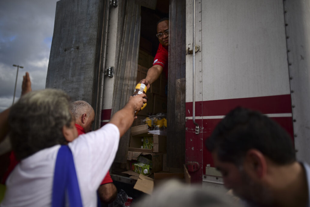 Residents receive aid supplies after suffering the previous day's magnitude 6.4 quake in Yauco, Puerto Rico, Wednesday, Jan. 8, 2020. More than 250,000 The quake that struck before dawn on Tuesday killed one person, injured nine others and knocked out power across the U.S. territory. More than 250,000 Puerto Ricans remained without water and another half a million without power, which also affected telecommunications.