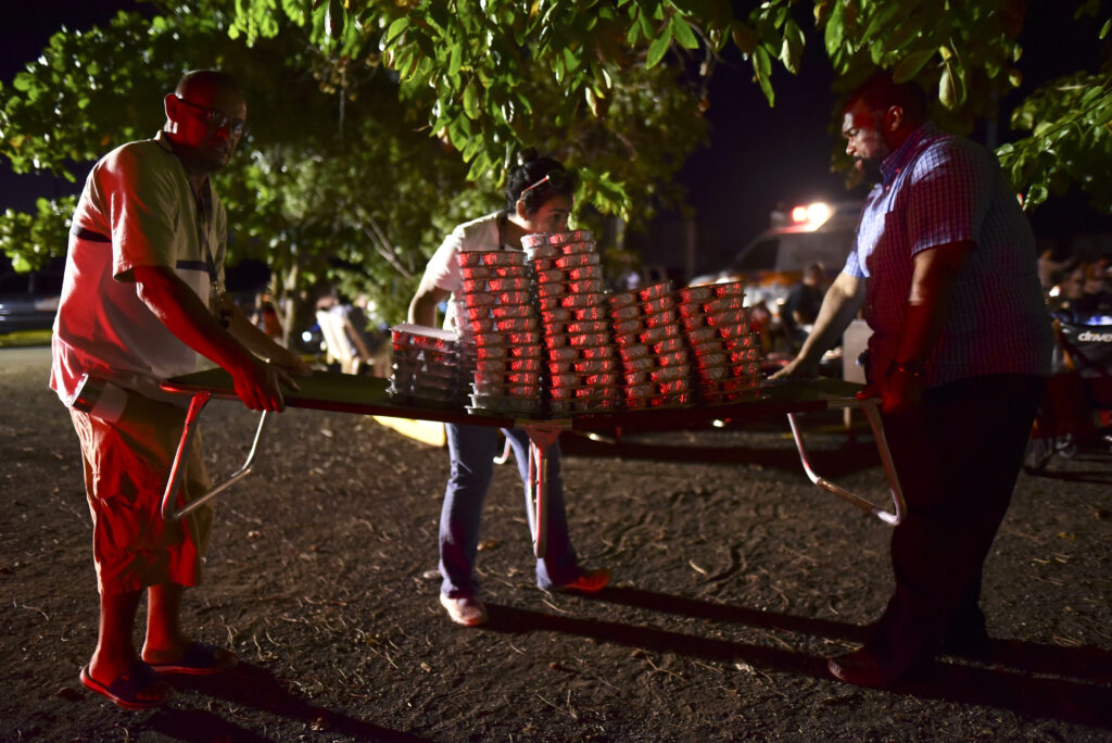 Volunteers distribute food to neighbors who remain outdoors using camping tents and portable lights for fear of possible aftershocks after a 6.4-magnitude earthquake struck in Guanica, Puerto Rico, Tuesday, Jan. 7, 2020. The quake was followed by a series of strong aftershocks, part of a 10-day series of temblors spawned by the grinding of tectonic plates along three faults beneath southern Puerto Rico.