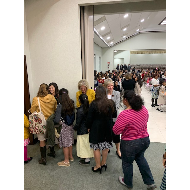 Sister Becky Craven, Sister Joy D. Jones, and Sister Jean B. Bingham greet members who attended a women's meeting for women ages 8 years old and up from various stakes in Mexico in December 2019.