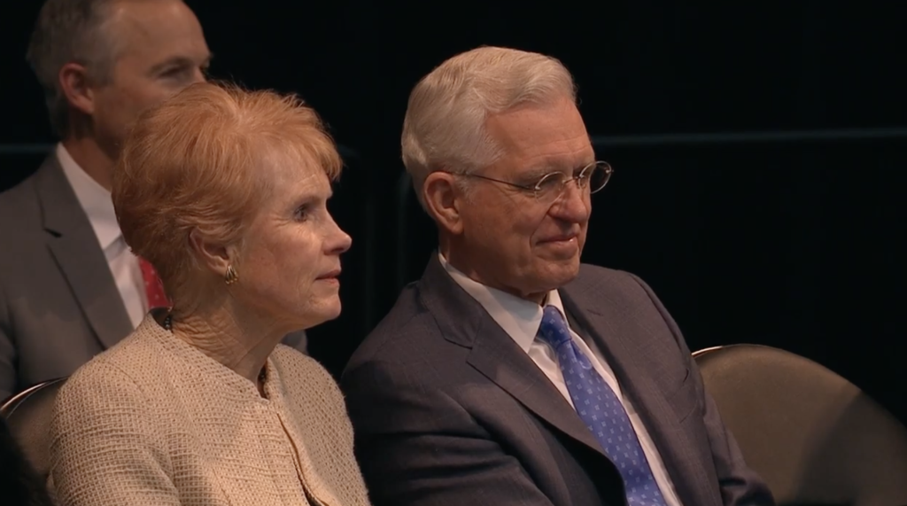 Elder D. Todd Christofferson of the Quorum of the Apostles sits on the stand next to his wife, Sister Kathy Christofferson, prior to speaking during a worldwide devotional broadcast from the UCCU Event Center in Orem, Utah, on Jan. 12, 2019.