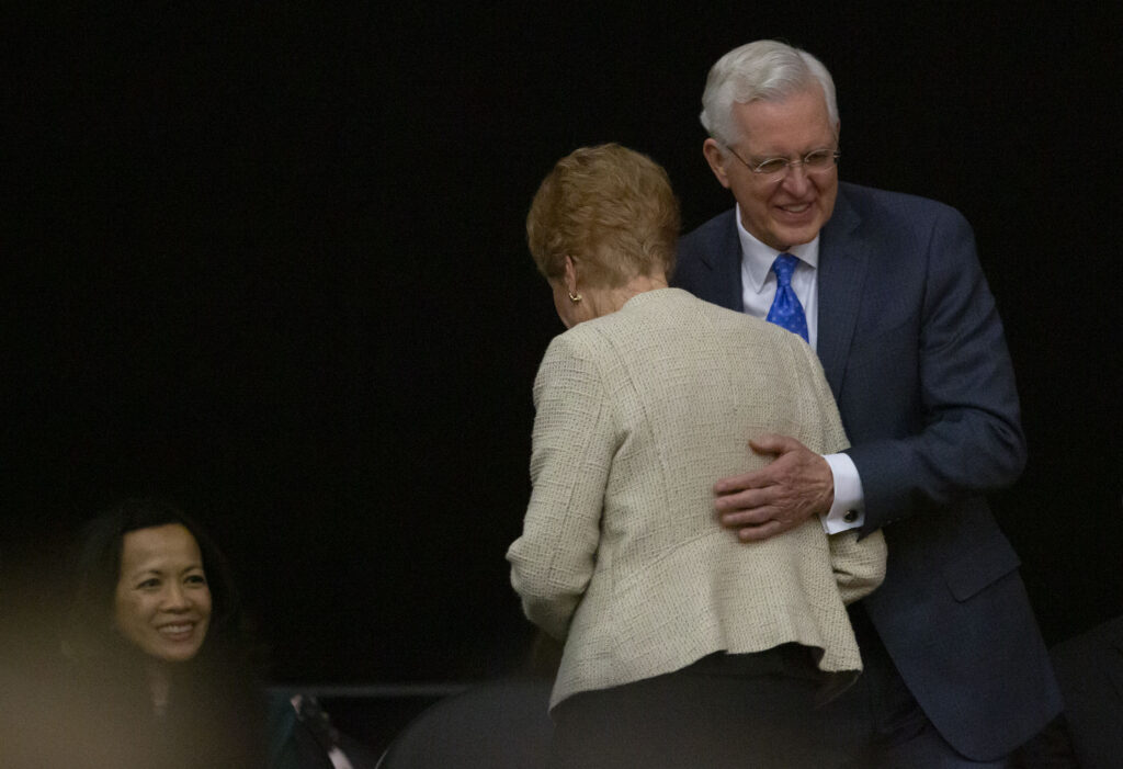Elder D. Todd Christofferson hugs Sister Katherine Christofferson following her address at a worldwide devotional broadcast from the UCCU Center at Utah Valley University in Orem on Sunday, Jan. 12, 2020.