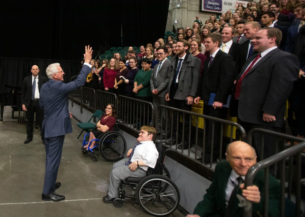 Elder D. Todd Christofferson waves to attendees during a worldwide devotional broadcast from the UCCU Center at Utah Valley University in Orem on Sunday, Jan. 12, 2020.