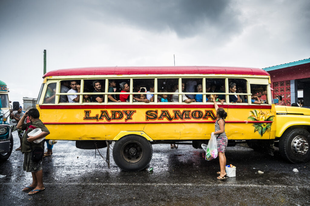 Samoans travel in a colorful bus.