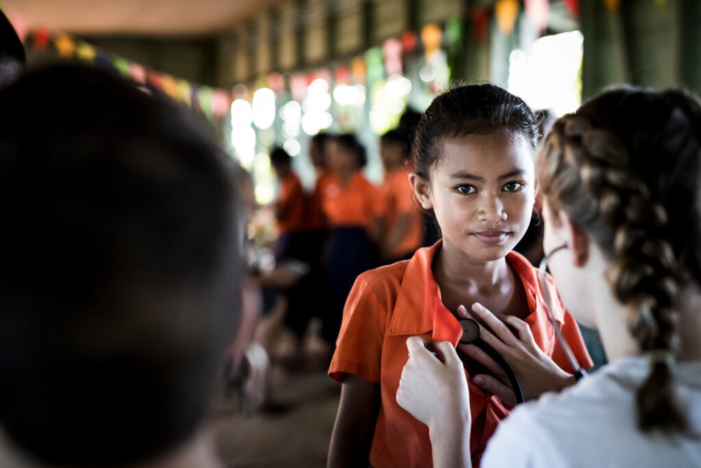 A BYU student volunteer examines a Samoan girl as part of the Rheumatic Relief program.