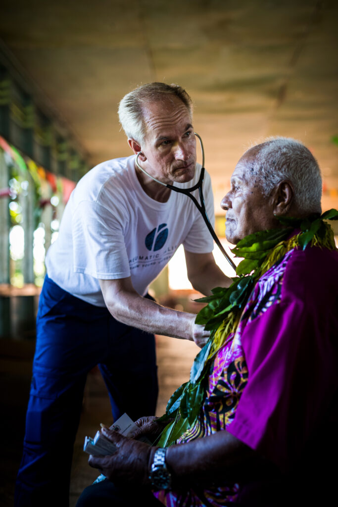 A BYU student volunteer examines a Samoan as part of the Rheumatic Relief program.