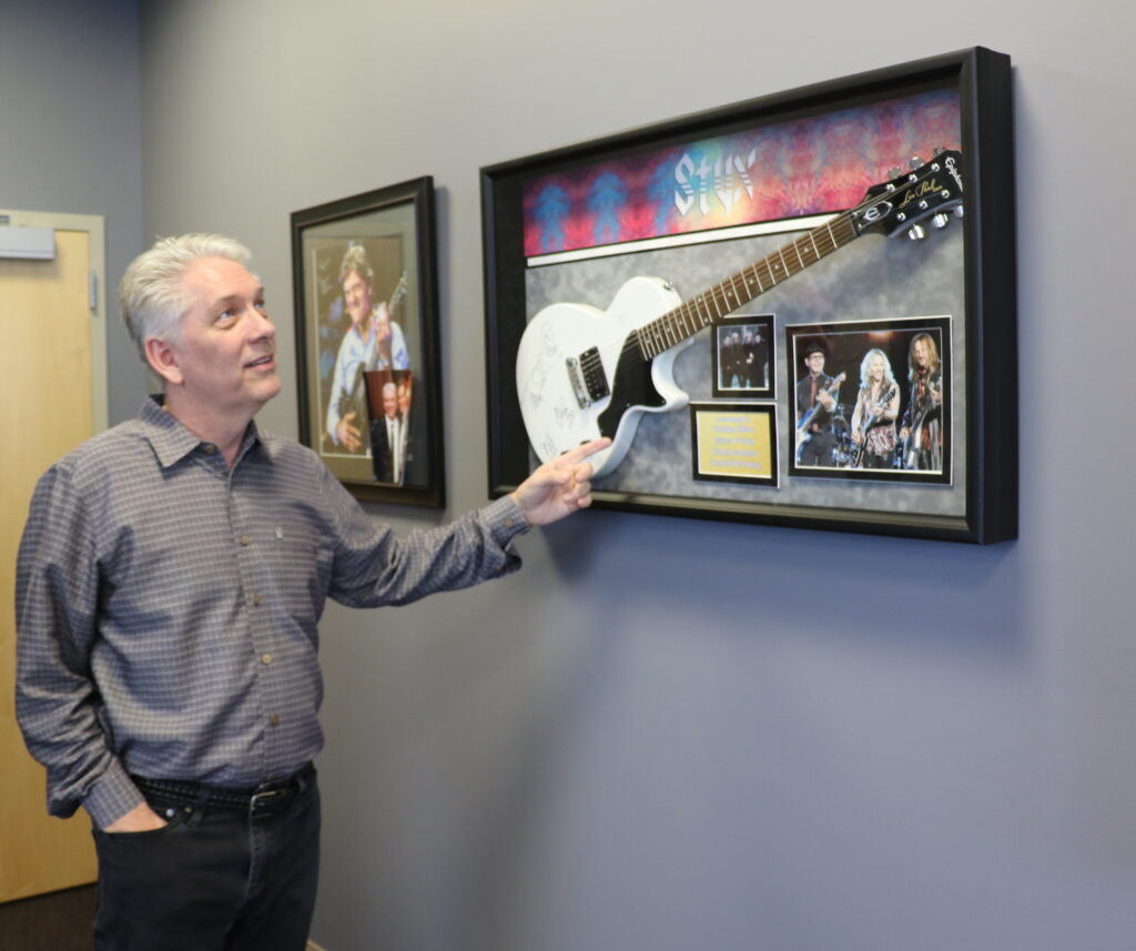 Latter-day Saint business executive Kevin Guest, in his West Valley City, Utah, office, points out signatures of Styx band members on a framed guitar. A skilled musician, Guest has performed with Styx front man Tommy Shaw.