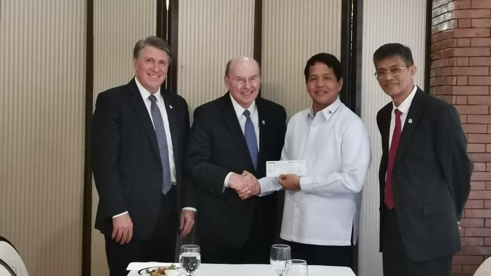 Days after the eruption of the Taal Volcano, Elder Quentin L. Cook presents a donation on behalf of the Church to Rolando Bautista, Department of Social Welfare and Development secretary.