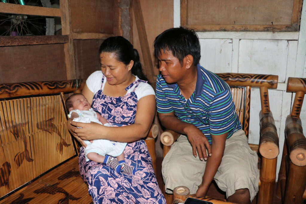 Analyn Esperas holds her infant son, Gemmer, in their home in Tacloban, Philippines, in 2017, while her husband, Gemmer, looks on. The Esperases lost their daughter, Annammer, when Typhoon Haiyan struck the Philippines on Nov. 8, 2013.