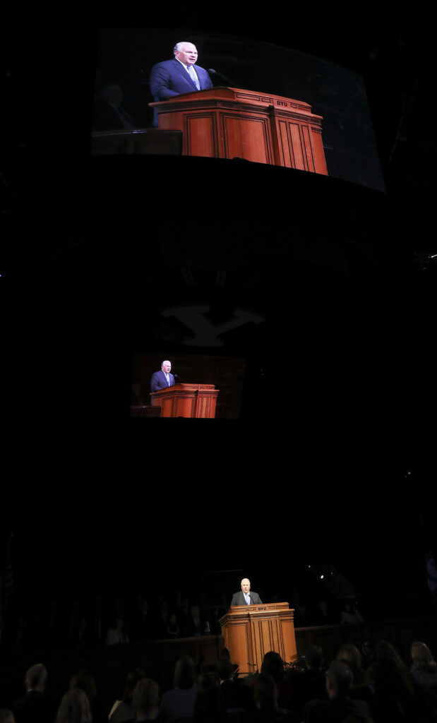 Stadium screens reflect Elder Ronald A. Rasband of the Quorum of the Twelve Apostles as he speaks during a Brigham Young University devotional at the Marriott Center in Provo, Utah, on Tuesday, Jan. 21, 2020.