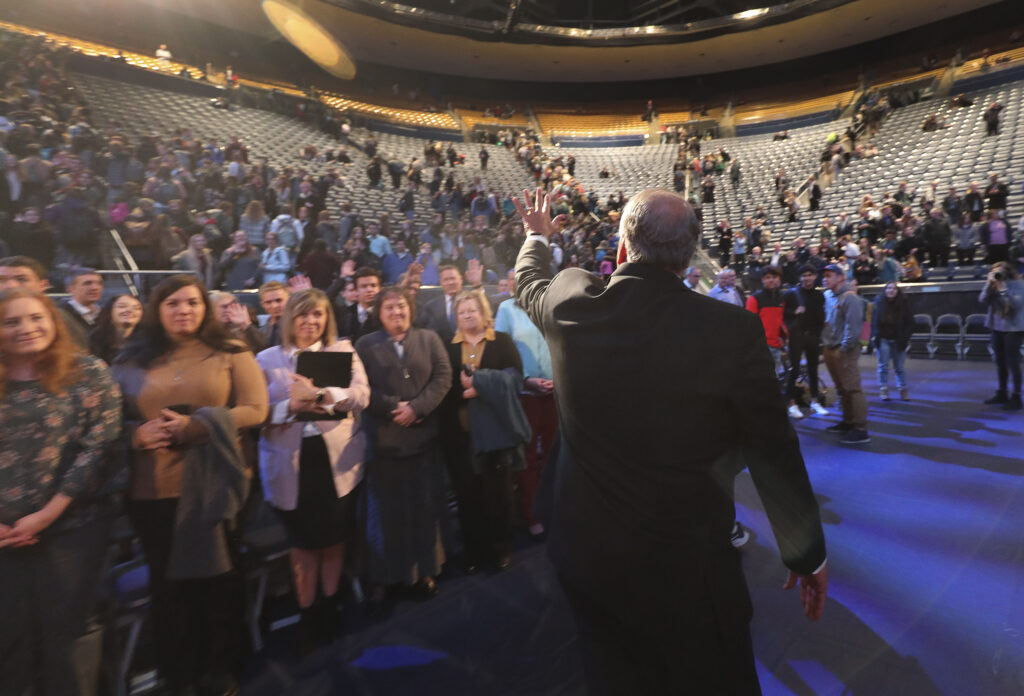 Elder Ronald A. Rasband of the Quorum of the Twelve Apostles waves to attendees after speaking at a Brigham Young University devotional at the Marriott Center in Provo, Utah, on Tuesday, Jan. 21, 2020.