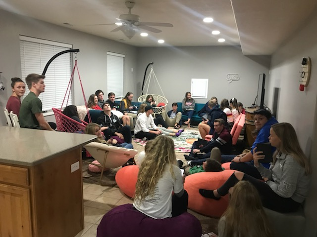 A crowd of teenagers enjoy studying the scriptures together in a weekly student-led scripture study group.