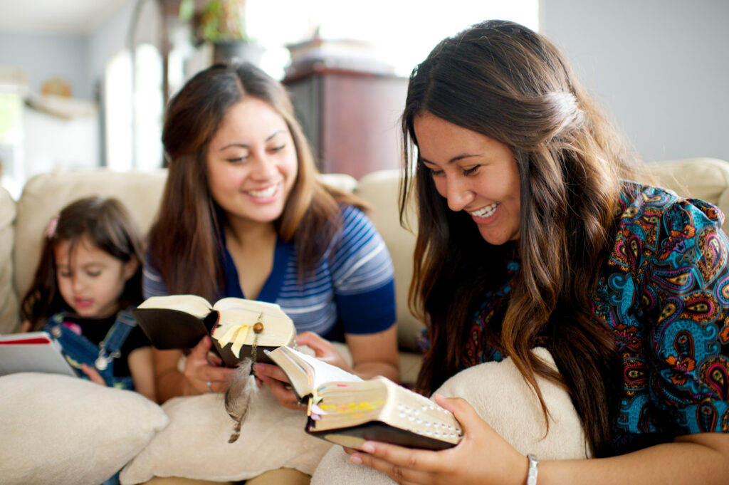 Two young women study the scriptures together at home on the couch.