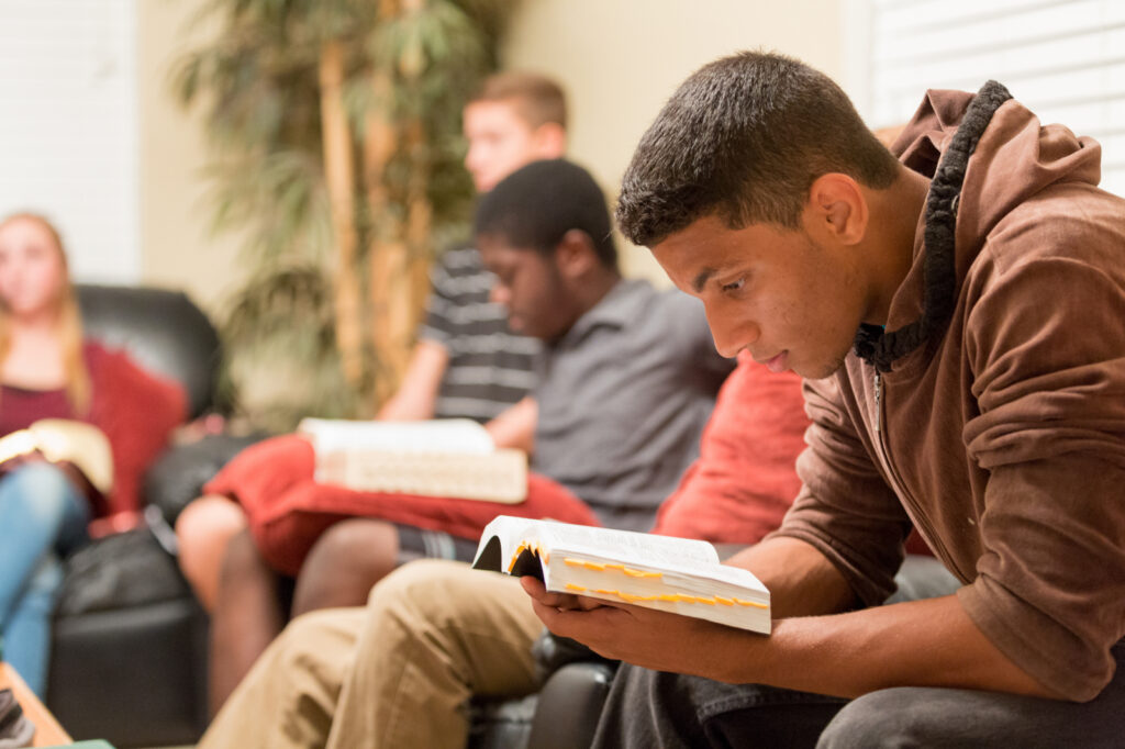 A group of young men study the scriptures together.