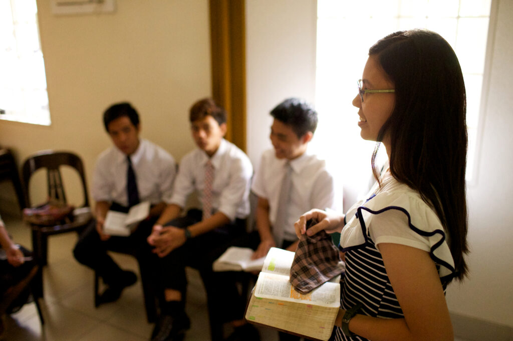 A Young Women class president leads a discussion from the scriptures during a ward youth council.