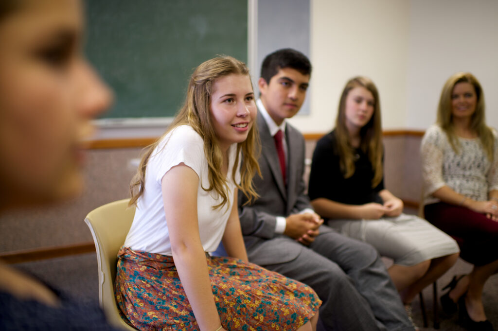 A Young Women class president shares her ideas during a ward youth council.