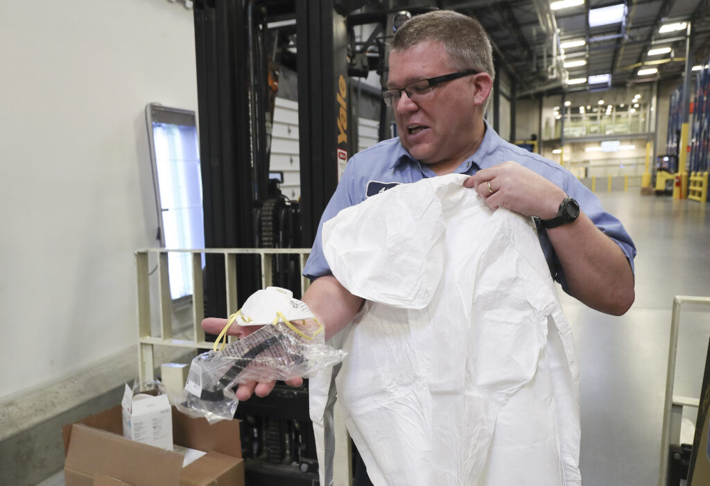 Warehouse worker Adam Hunt holds a respirator mask, protective goggles and protective suit as The Church of Jesus Christ of Latter-day Saints contribute aid to China in Salt Lake City on Wednesday, Jan. 29, 2020.