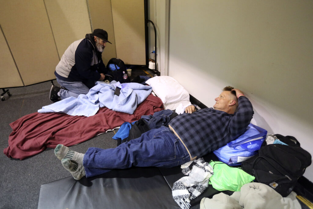 Clinton Hayes and Michael Huffman get settled in at Puyallup Nazarene Church where they and other homeless people will sleep for the night, as part of Freezing Nights, in Puyallup, Wash., on Sunday, Jan. 26, 2020.