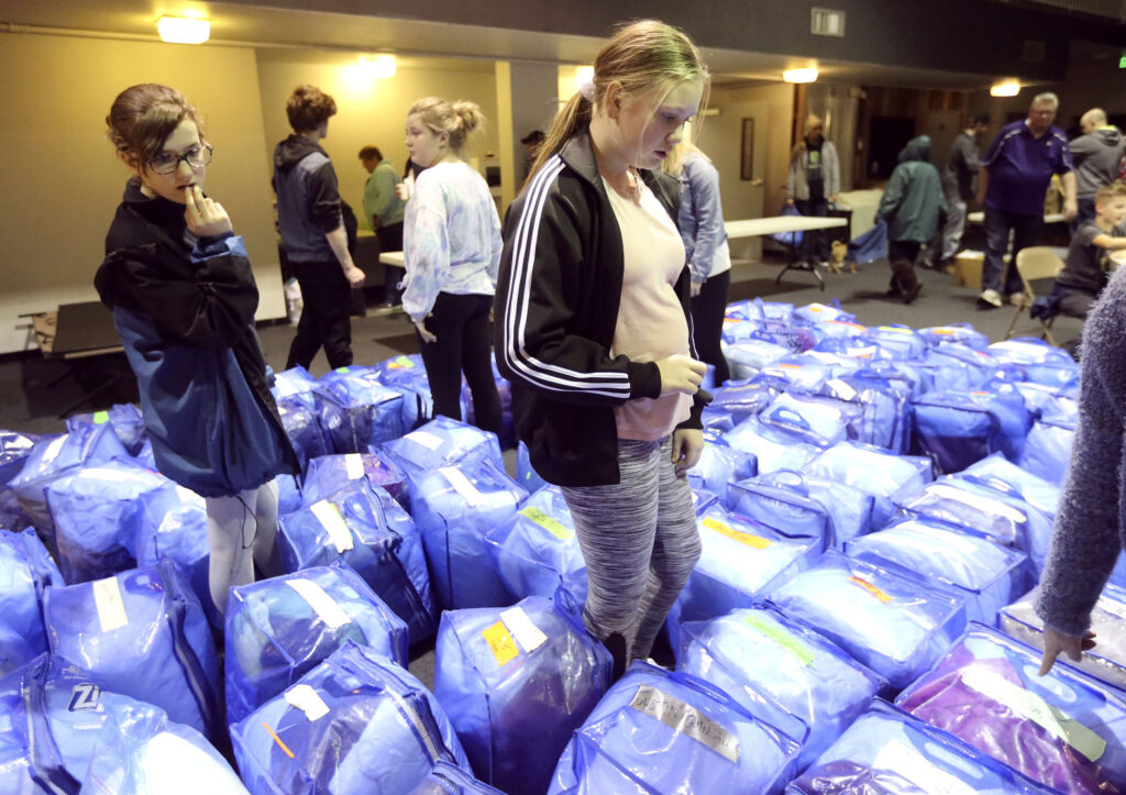Jordan Wilkie looks through labeled bags of bedding as homeless arrive at Puyallup Nazarene Church, and take their bedding to cots or mats to sleep in Puyallup, Wash., on Sunday, Jan. 26, 2020. Wilkie's father is homeless, and sleeps in his van. Wilkie's grandmother volunteers and transports the homeless every Sunday night to a church where they can sleep while her father helps set up the cots for other homeless.