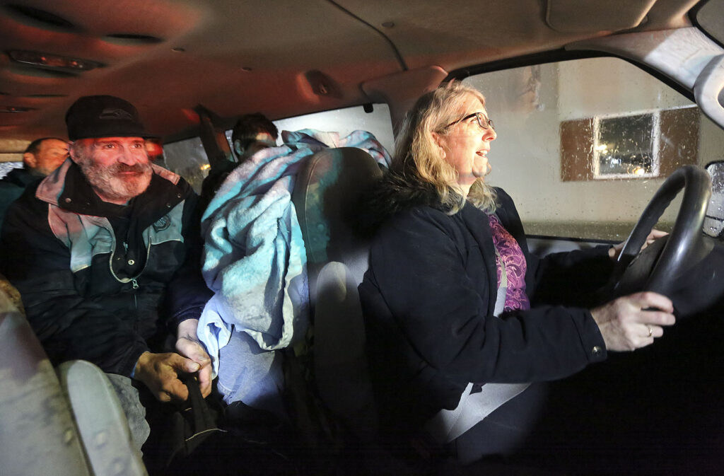 Diane Kienholz drives Clinton Hayes and other homeless people to Puyallup Nazarene Church, so they can sleep for the night, in Puyallup, Wash., on Sunday, Jan. 26, 2020.