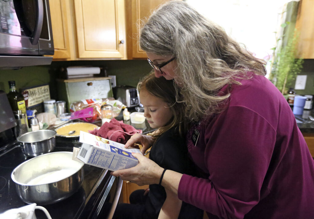 Diane Kienholz helps her granddaughter Jade Wilkie make a belated birthday cheesecake for Kienholz's son and Wilkie's father, Jesse Kinman, at Kienholz's home in Puyallup, Wash., on Sunday, Jan. 26, 2020.