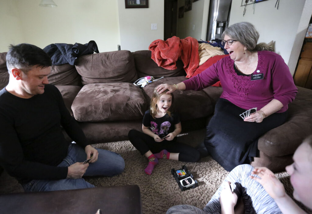 Jesse Kinman, his daughter Jade Wilkie, mother Diane Kienholz, and daughter Jordan Wilkie play Uno at Kienholz's home in Puyallup, Wash., on Sunday, Jan. 26, 2020. Kinman is homeless but often spends Saturday night at his mother's house with his daughters.
