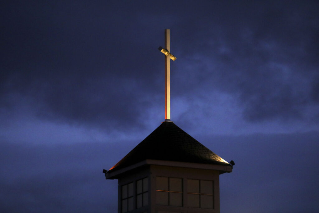 A cross is illuminated on top of Puyallup Nazarene Church, which is housing the homeless in partnership with Freezing Nights in Puyallup, Wash., on Sunday, Jan. 26, 2020.