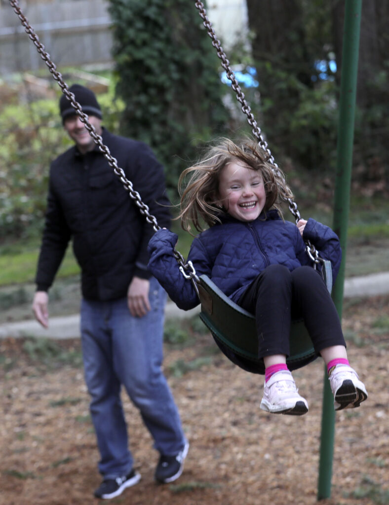 Jesse Kinman pushes his daughter, Jade Wilkie, on a swing at Ranier Woods Park, near Kinman's mother's home in Puyallup, Wash., on Sunday, Jan. 26, 2020. Kinman is homeless, so he and his daughters spend a lot of time in parks when they are together.