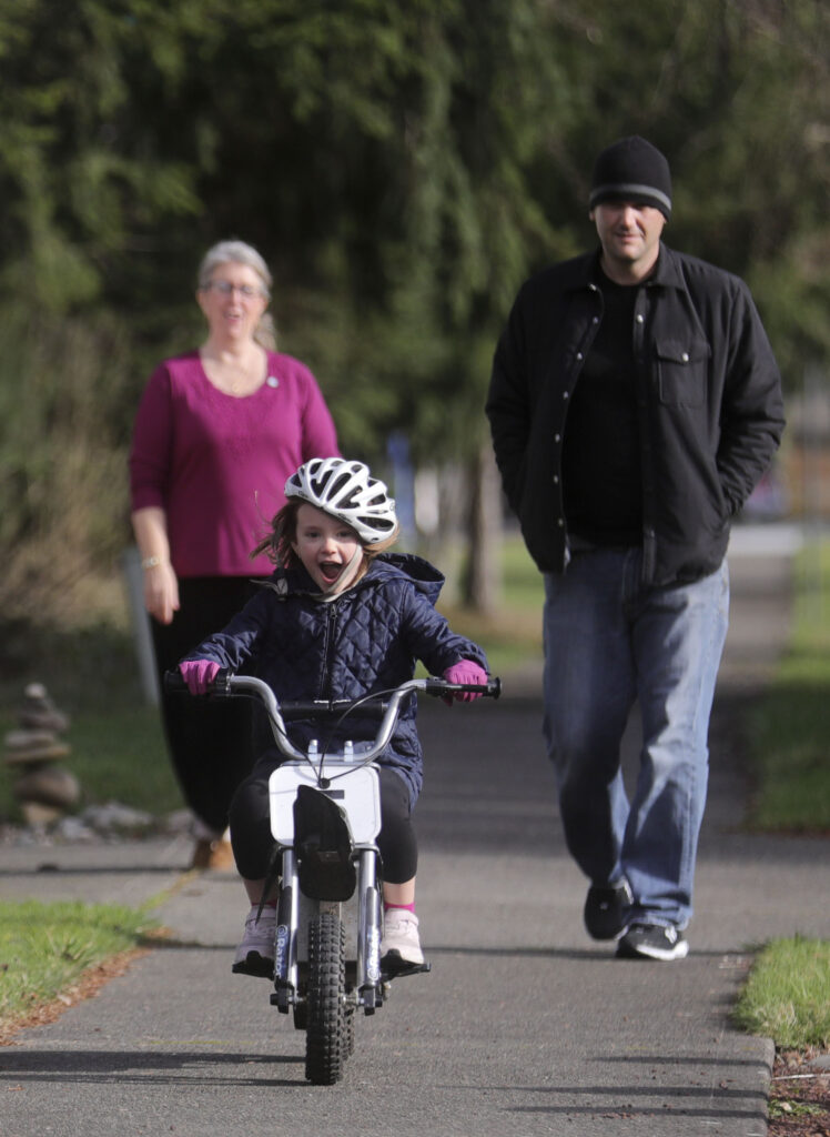 Jade Wilkie rides a bike as her grandmother, Diane Kienholz, and father Jesse Kinman follow in Puyallup, Wash., on Sunday, Jan. 26, 2020.