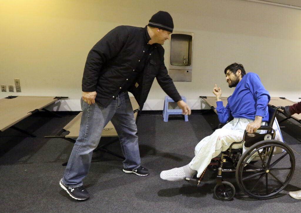 Jesse Kinman welcomes Ivan Esparza to the Puyallup Nazarene Church as Esparza picks out a cot to sleep on, as part of Freezing Nights, in Puyallup, Wash., on Sunday, Jan. 26, 2020. Kinman helps volunteer with Freezing Nights and is also homeless himself. Kinman sleeps in his van outside of Walmart.